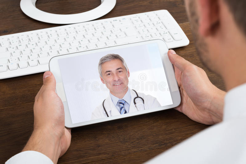 Businessperson Videochatting With Senior Doctor stock photography