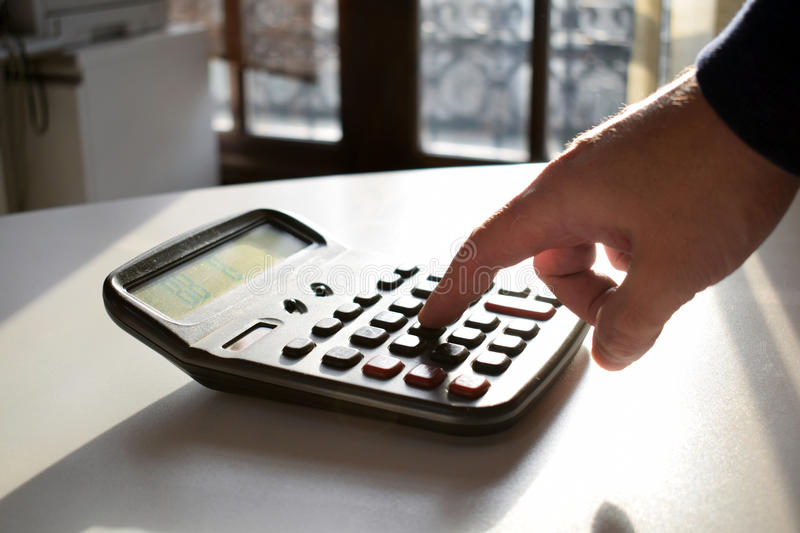 Businessperson working in office.Man hand with calculator at workplace. royalty free stock image