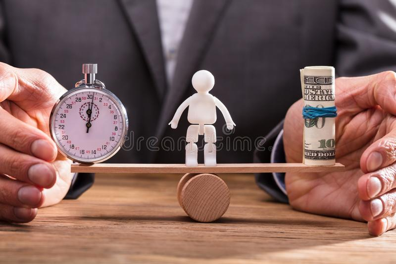 BusinesspersonBalancing Stopwatch And sedlar arkivbilder