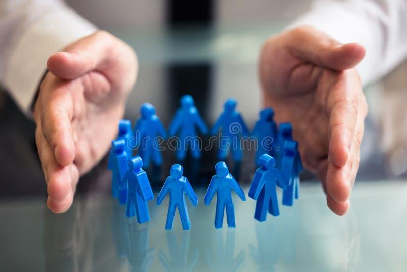 Businesspersonen Protecting Blue Human figurerar att bilda cirkeln arkivfoto