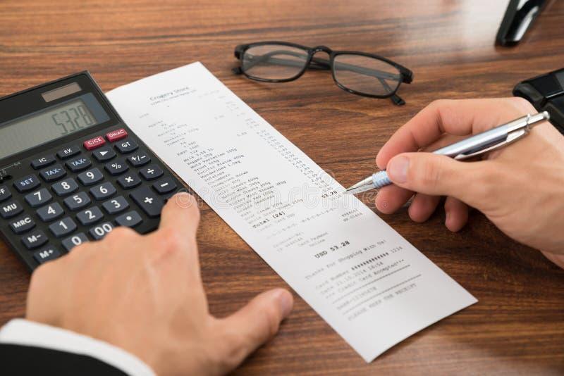 Businesspersonen räcker beräkning av kostnader på skrivbordet royaltyfri foto