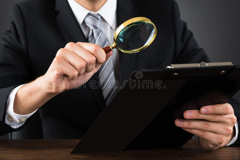 BusinesspersonInspecting Document With förstoringsglas arkivfoto