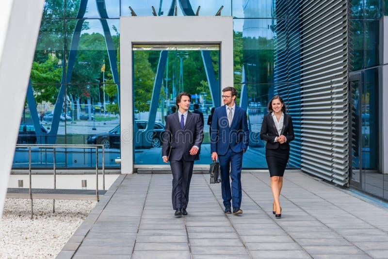 Businesspersons confiados que hablan delante del edificio de oficinas moderno Los hombres de negocios y la empresaria tienen nego foto de archivo