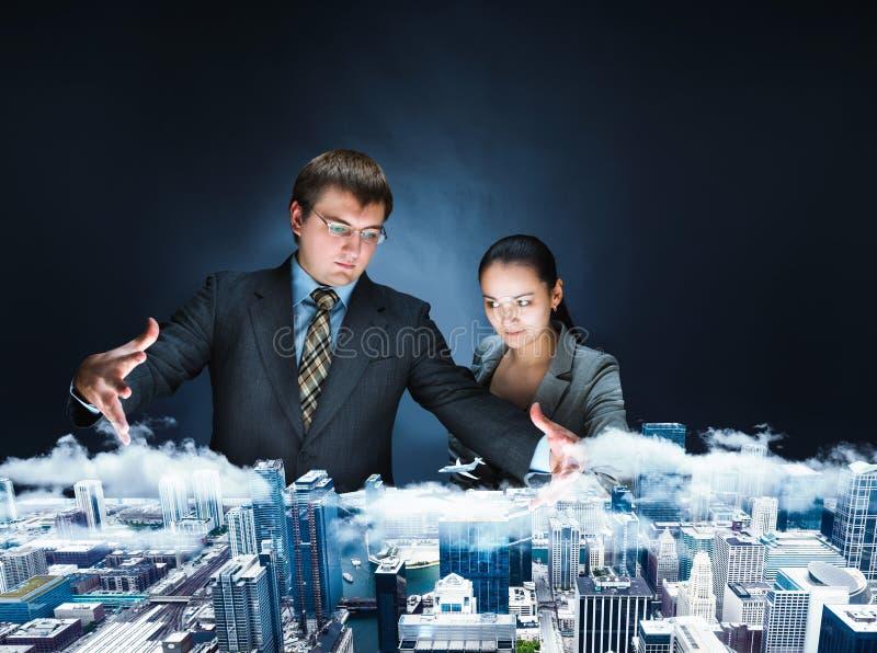 Businesspersons puissants regardant sur le modèle de la ville photographie stock
