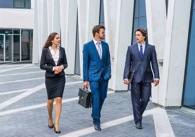 Businesspersons sicuri che parlano davanti all'edificio per uffici moderno Gli uomini d'affari e la donna di affari hanno affare fotografia stock