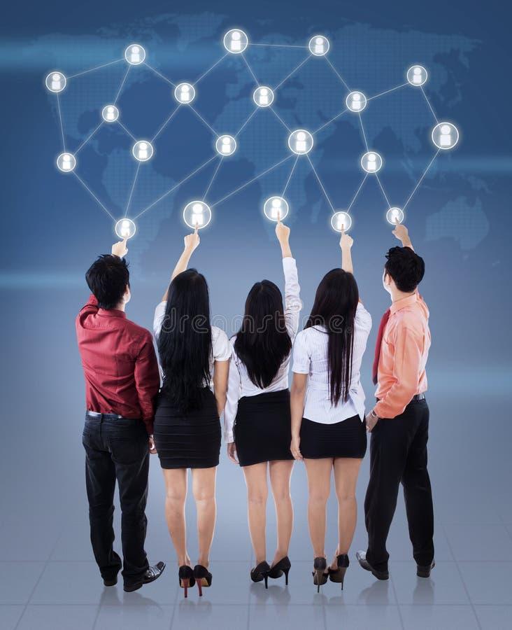 Businessteam нажимая социальную сеть стоковая фотография