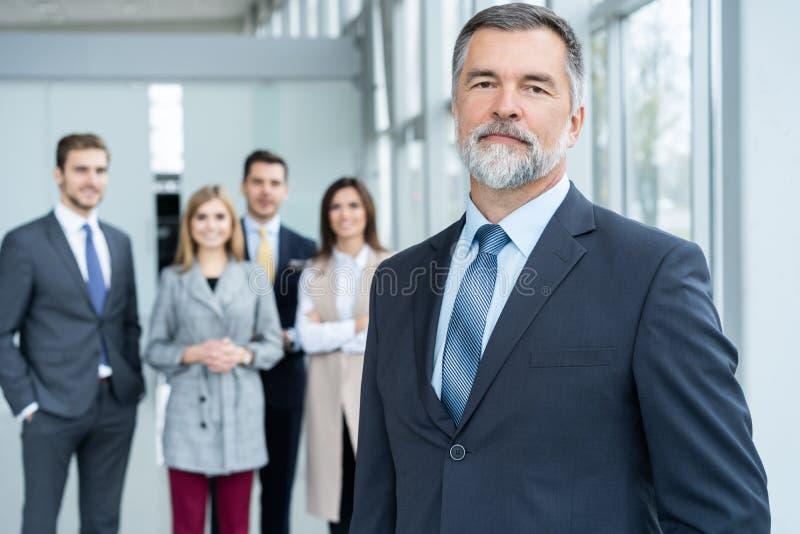 Businessteam in bureau, Gelukkige Hogere Zakenman in Zijn Bureau bevindt zich voor hun team royalty-vrije stock fotografie