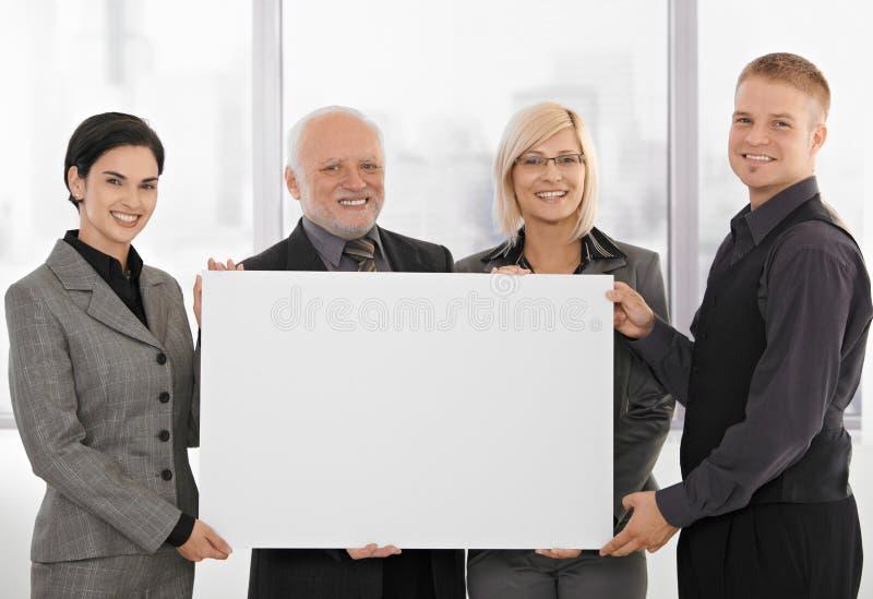 Businessteam, das unbelegtes Plakat anhält stockbild