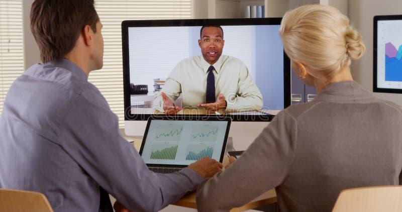 Businessteam die aan manager in een videoconferentie luisteren stock foto