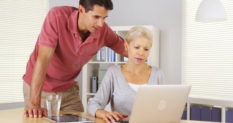 Businessteam die gelukkig in het bureau werken stock afbeeldingen