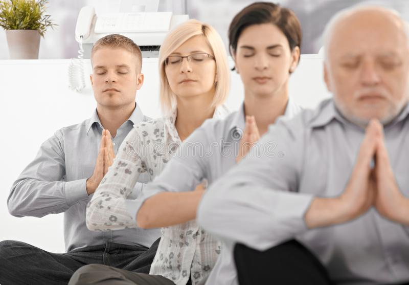 Businessteam doing yoga exercise. In office together, sitting on floor with eyes closed royalty free stock photo