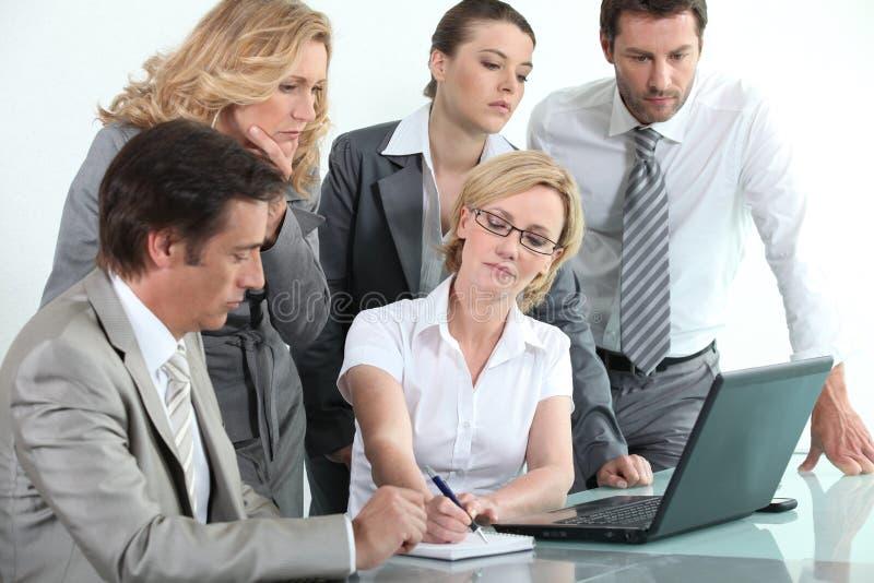 Businessteam em torno de um portátil fotografia de stock