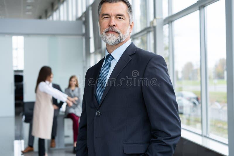 Businessteam i regeringsställning, den lyckliga höga affärsmannen i hans kontor står framme av deras lag arkivbild