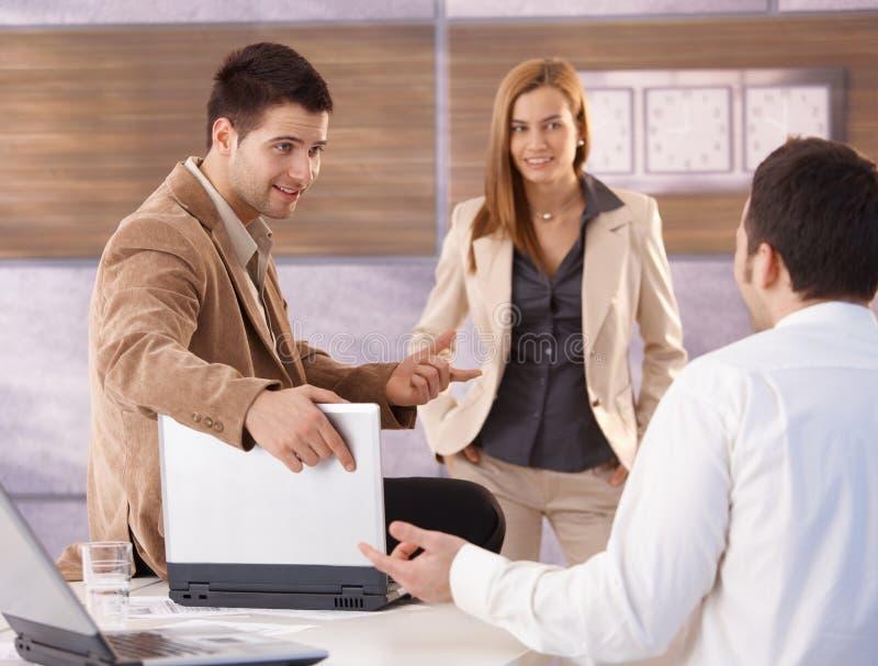 Businessteam joven que habla en la sonrisa de la oficina foto de archivo libre de regalías