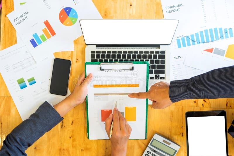 Businessteam met pen en de grafiek ter beschikking analyseren het werk L stock afbeelding