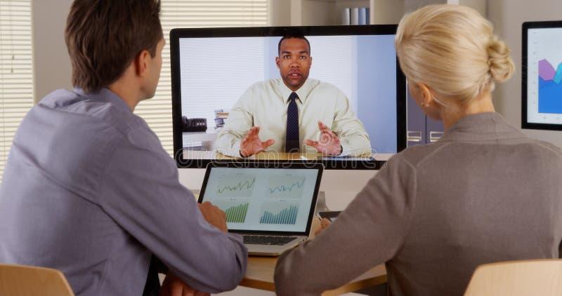 Businessteam que escucha el encargado en una videoconferencia imagen de archivo