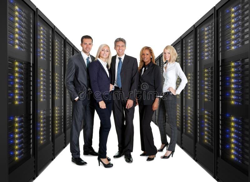 Businessteam que se coloca en el frente de los estantes del servidor fotos de archivo