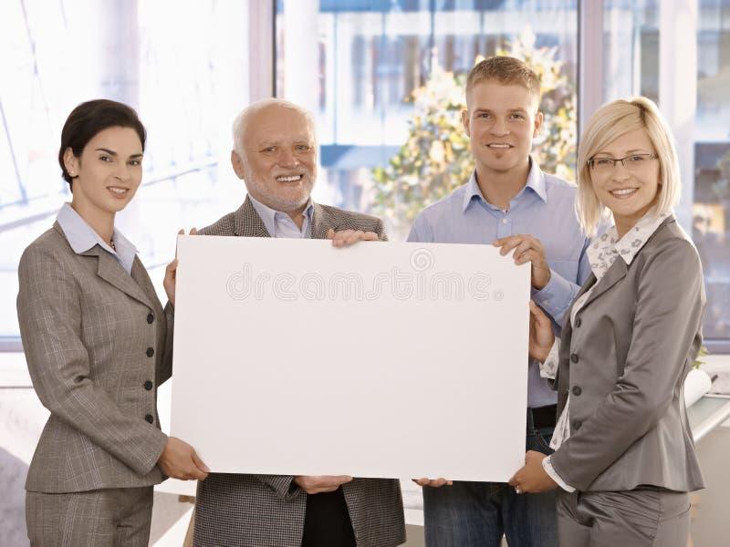 Businessteam que sostiene el cartel en blanco para el espacio de la copia fotografía de archivo
