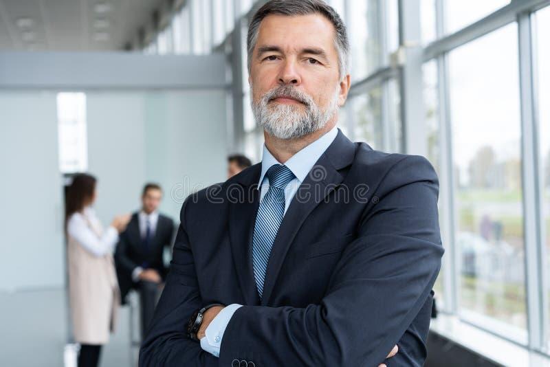 Businessteam w biurze, Szczęśliwy Starszy biznesmen w Jego biurze stoi przed ich drużyną zdjęcia stock