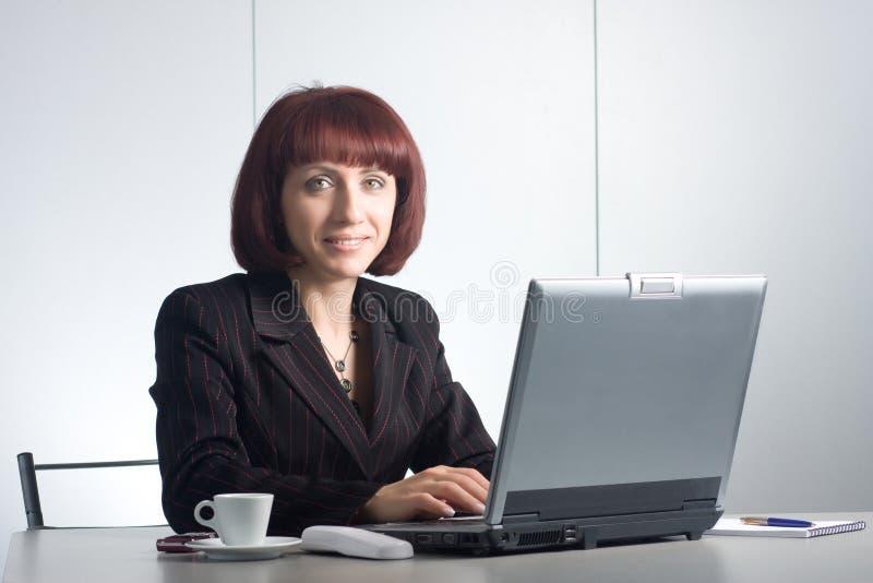 businesswomаn hermoso detrás de una mesa imágenes de archivo libres de regalías