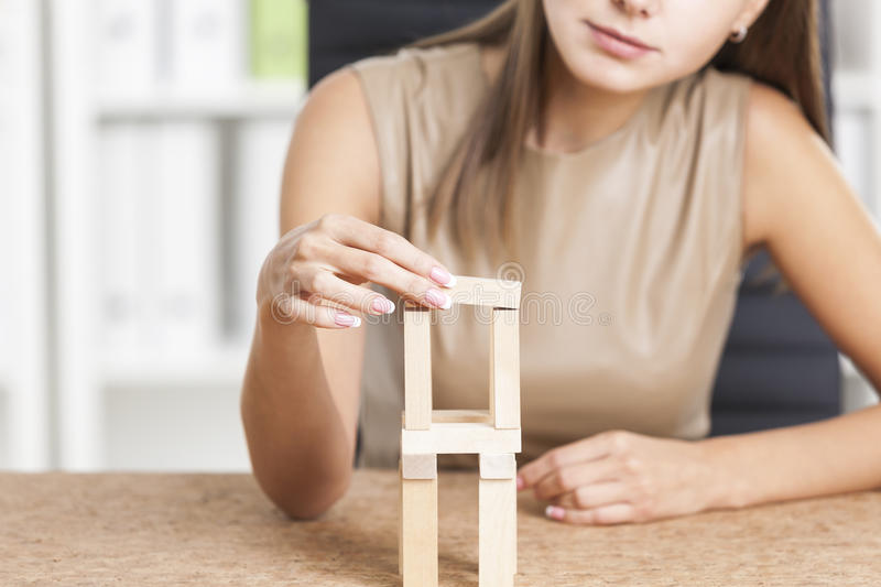 Businesswoman's hands playing with wood bricks. Businesswoman's hands playing with wooden bricks at her workplace in a white office. Concept of a stock images