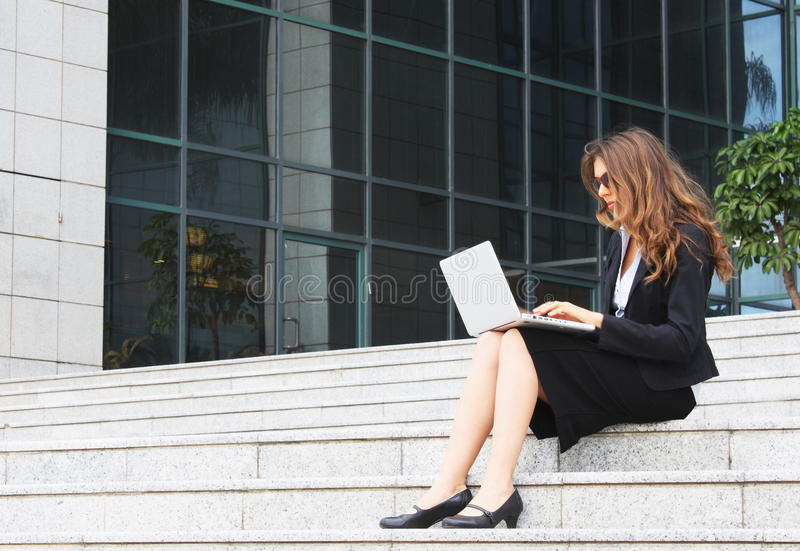 Businesswoman. Sitting on stairs with laptop stock photo