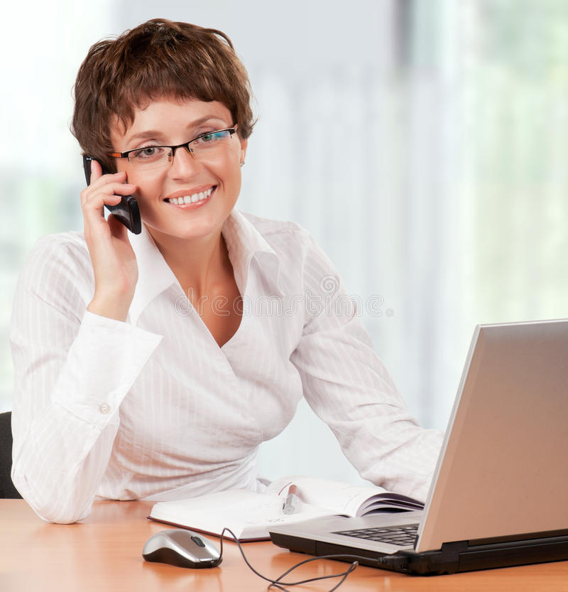 Businesswoman. Beautiful businesswoman working with laptop holding a mobile at her office royalty free stock image