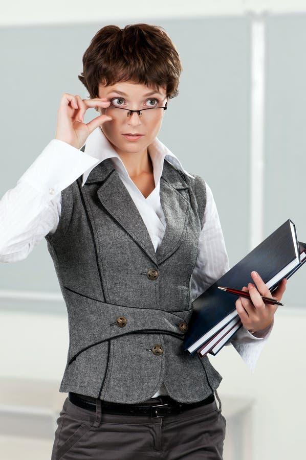 Businesswoman. Portrait of a beautiful caucasian businesswoman or teacher with books stock image