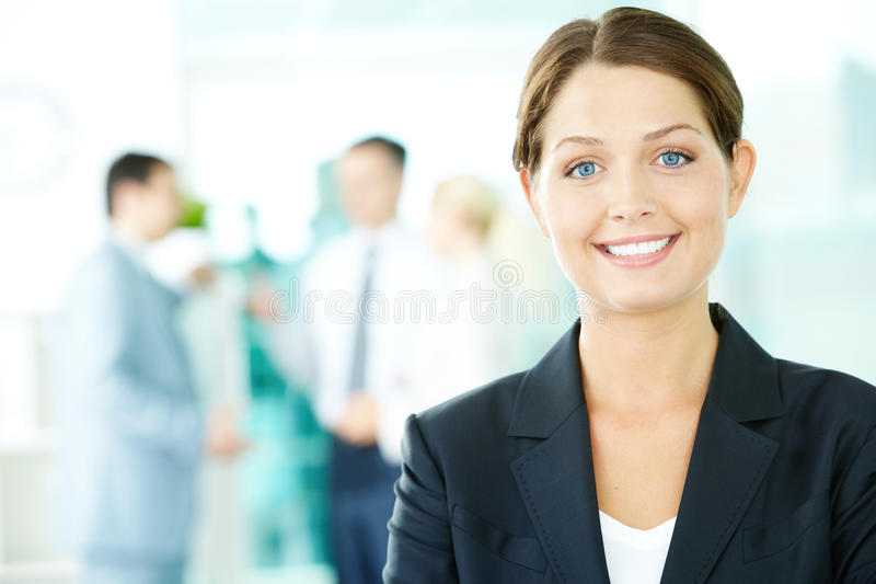 Businesswoman. A beautiful businesswoman looking at camera in working environment royalty free stock images