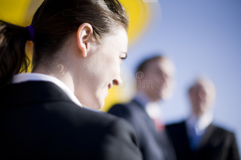 Businesswoman. Looking forward with two businessmen looking at camera royalty free stock photo