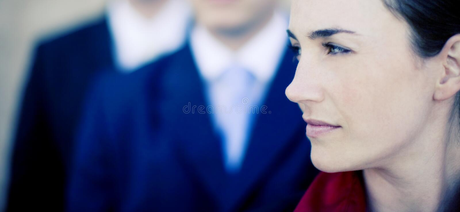Businesswoman. Profile of beautiful businesswoman with two businessmen in the background stock photos