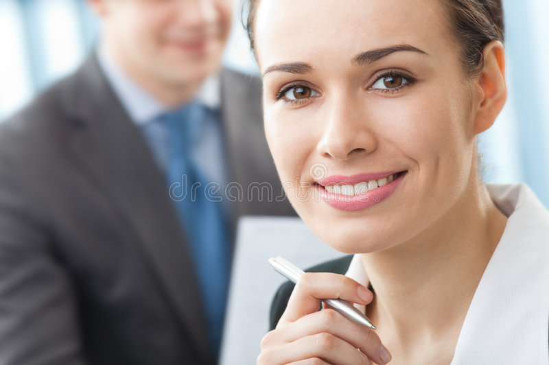 Businesswoman. And colleague on background, at office stock images