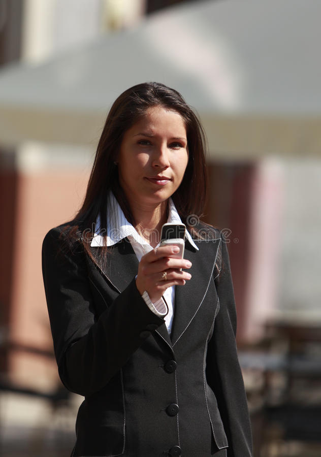 Businesswoman. Checking her mobile phone in a city stock image