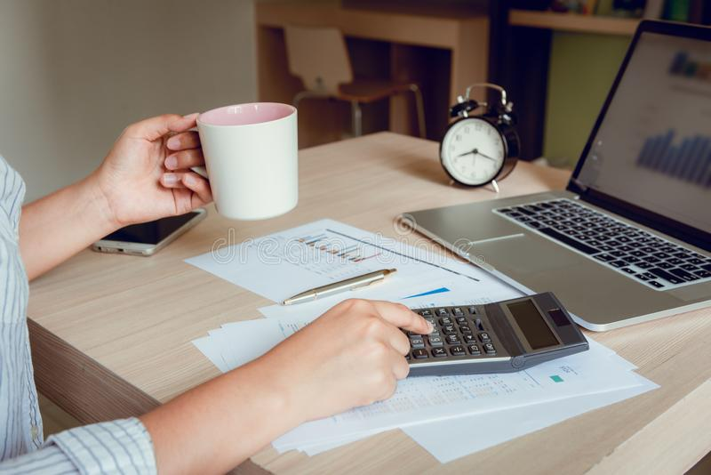 Businesswoman of accountant analysis checking financial statement in office while holding a cup of coffee and other hand pressing royalty free stock photo