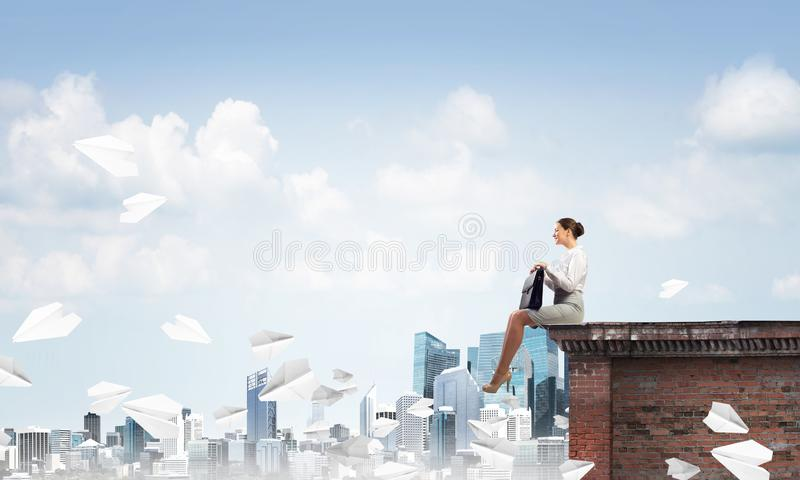 Businesswoman or accountant on building top and paper planes flying around. Mixed media royalty free stock photos