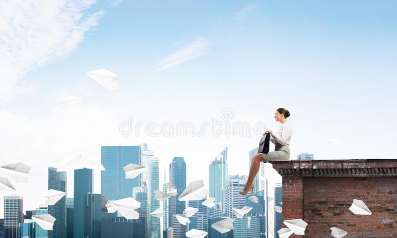 Businesswoman or accountant on building top and paper planes flying around. Mixed media stock image