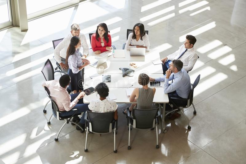 Businesswoman addressing colleagues at table, elevated view stock photography