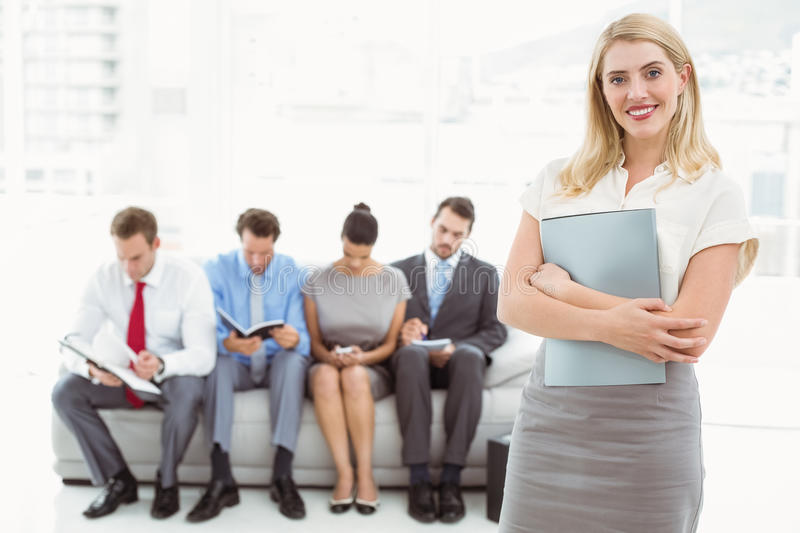 Businesswoman against people waiting for interview. Portrait of businesswoman against people waiting for job interview in office stock photos