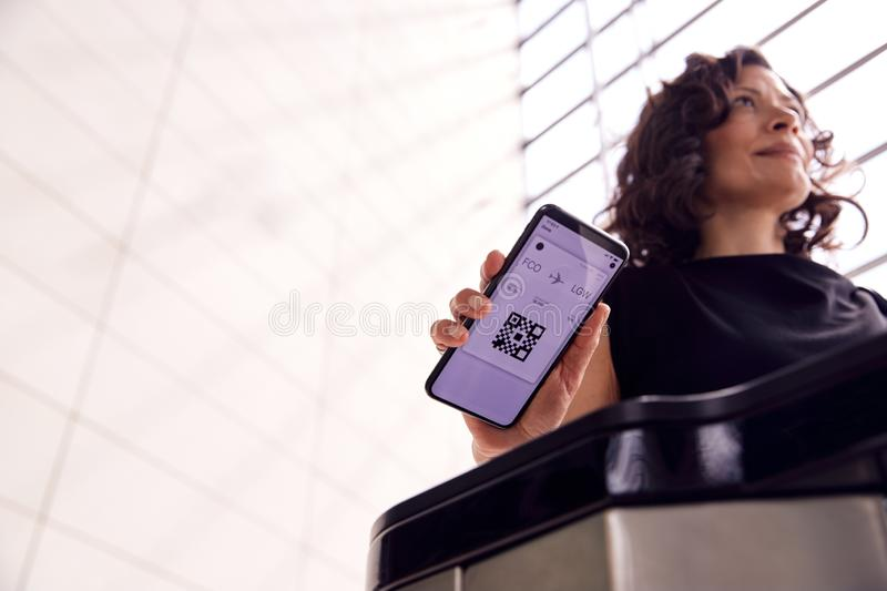Businesswoman In Airport Departure Lounge Scanning Digital Boarding Pass On Smart Phone royalty free stock photos