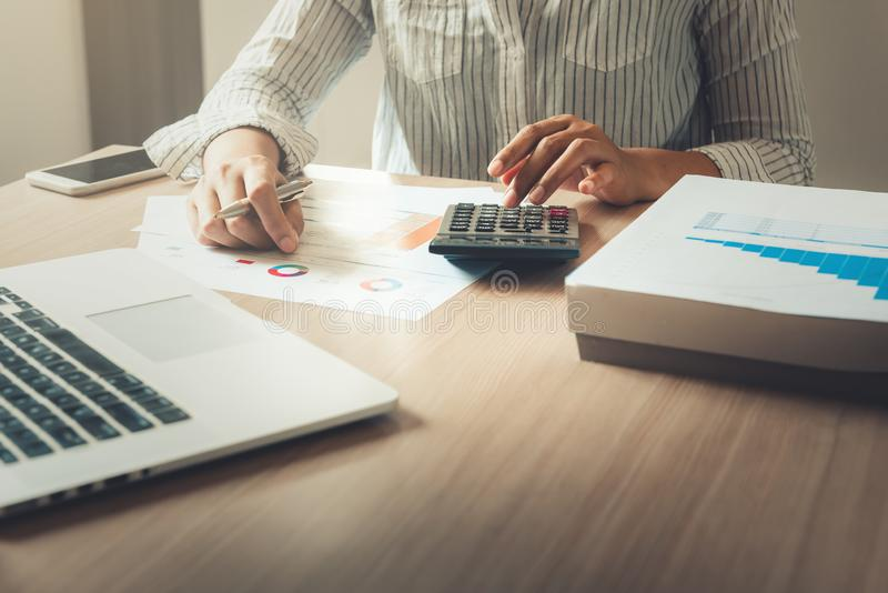 Businesswoman is analyzing of financial and planning calculation for investment on table desktop., Accounting tax document. Information for balancing budget and stock image