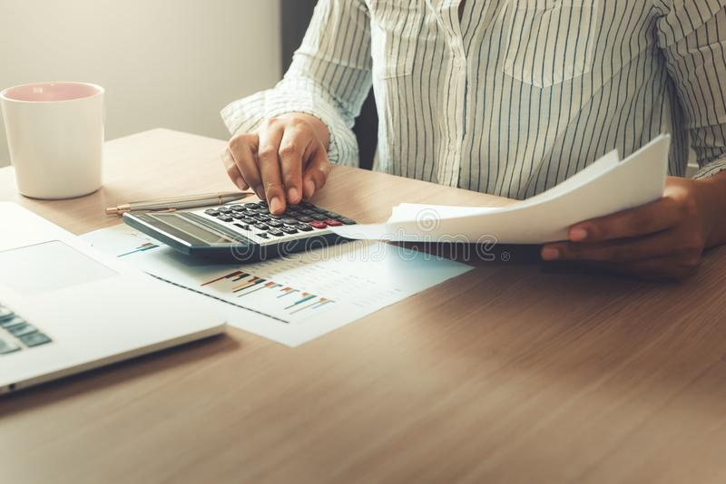 Businesswoman is analyzing of financial and planning calculation for investment on table desktop., Accounting tax document. Information for balancing budget and royalty free stock photography
