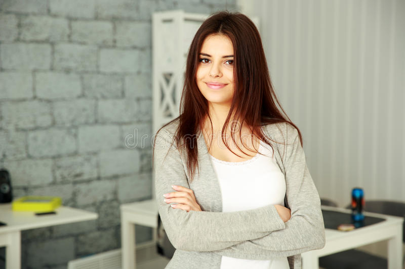Businesswoman with arms folded standing. Young smiling businesswoman with arms folded standing at office stock image