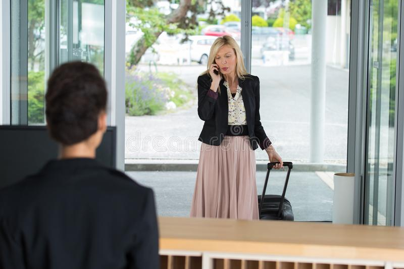 Businesswoman arriving at hotel welcomed by receptionist. Businesswoman arriving at the hotel welcomed by receptionist royalty free stock images