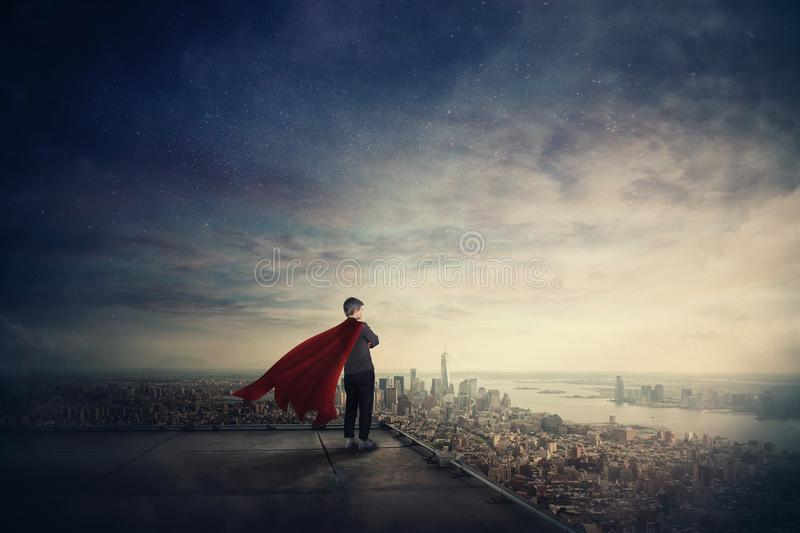 Businesswoman as confident superhero with red cape stands on the rooftop looking over city horizon. Ambition and business success royalty free stock image