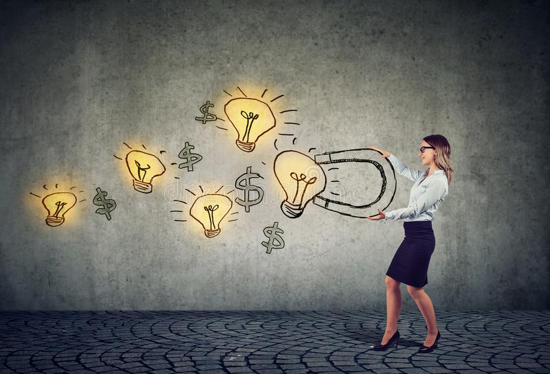 Businesswoman attracts bright ideas light bulbs with a big magnet stock images
