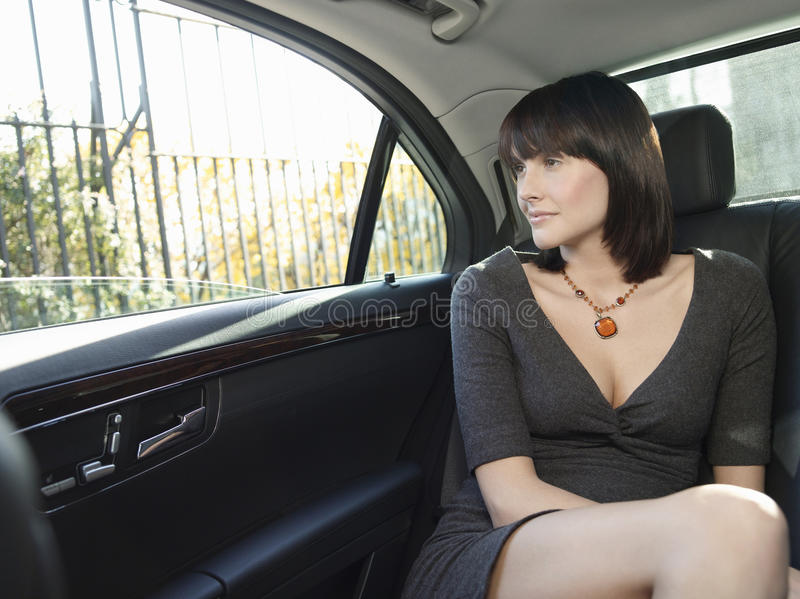 Businesswoman In Back Seat Of Car Looking Out Window Stock
