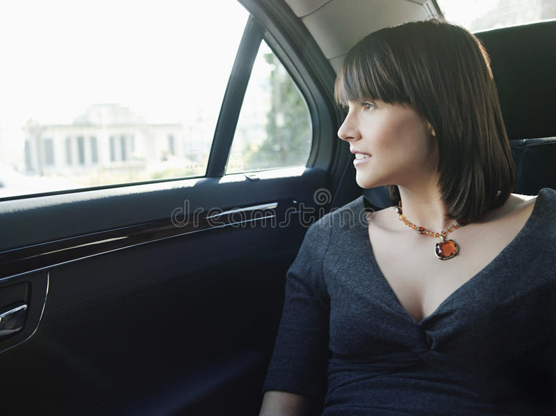 Businesswoman At Back Seat Of Car Looking Out Window royalty free stock photo