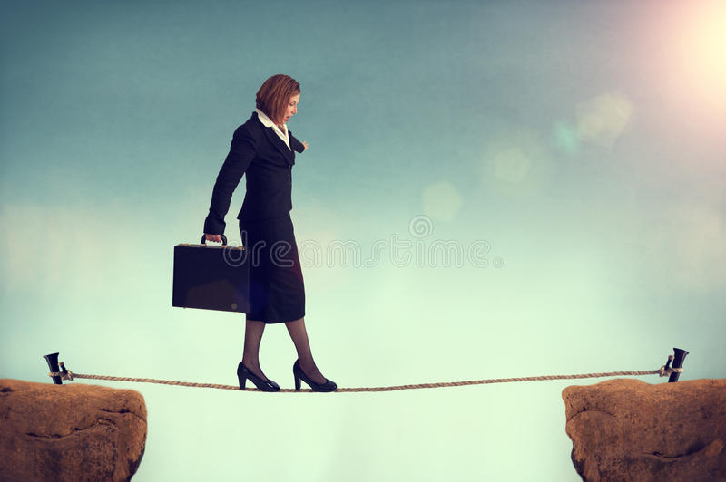 Businesswoman balancing on a tightrope. Conquering adversity concept royalty free stock image