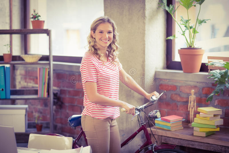 Businesswoman with bicycle standing in office stock image