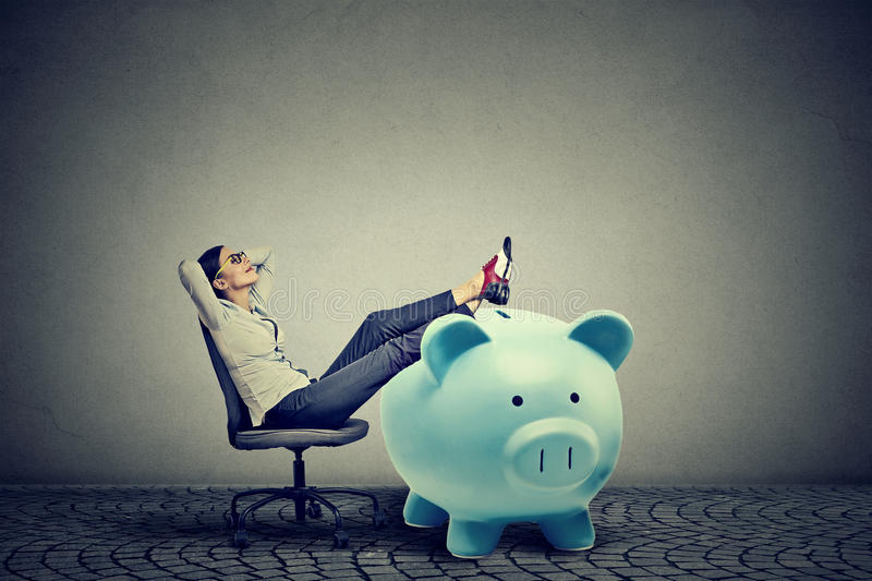 Businesswoman with big piggy bank relaxing sitting on chair. Young businesswoman with big piggy bank relaxing sitting on chair stock photography